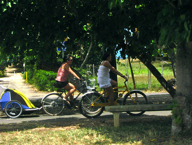 Mom with kiddie trailer, and a friend bike along the path  North Shore, Oahu, Hawaii