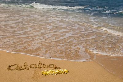 Sunset BeachPlumeria lei, Aloha written in the sand at sunset