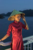 Vietnamese woman in a red cheongsam on board ship in the evening, Ha Long Bay, north Vietnam