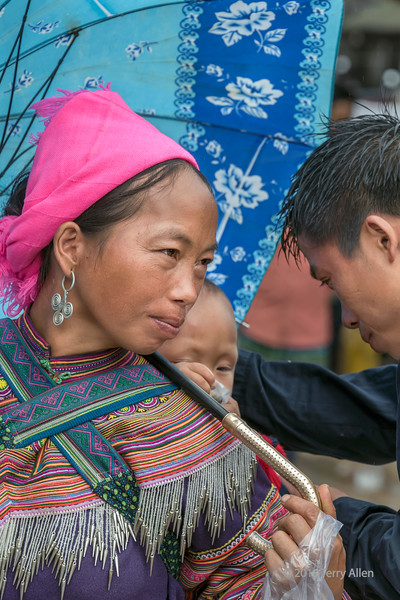 Tender moment, Flower Hmong woman, husband and baby, Cuy Ly market in the rain, Sa Pa, Vietnam