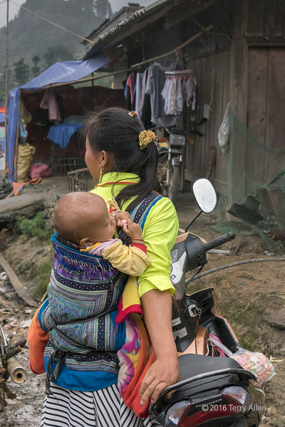 Hmong mother and baby by motorbike on a rainy day, Coc Ly market, Sa Pa, north Vietnam