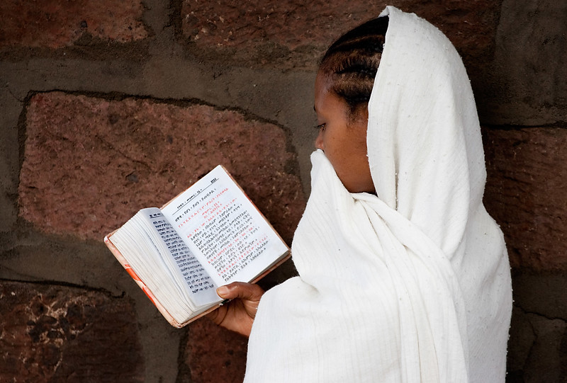 Pilgrim reading her Bible at Bet Medhane Alem church - Lalibela