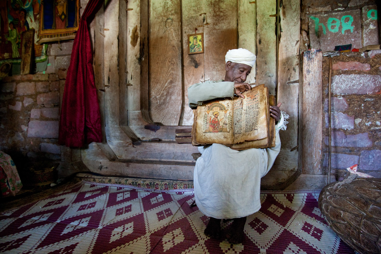 Priest presenting an old book, Debre Maryam Monastery - Lake Tana
