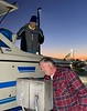 Jim McKeeman, feeding quarters into the water supply machine, as Walt looks on.<br /> Huntington Harbor, California<br /> January 9, 2021