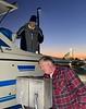 Jim McKeeman, feeding quarters into the water supply machine, as Walt looks on.<br /> Huntington Harbor, California<br /> January 9, 2021