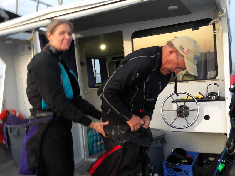 Nannette & Bill Van Antwerp donning drysuits.<br /> Giant Stride<br /> Black Water (night) dive, off Palos Verdes, California