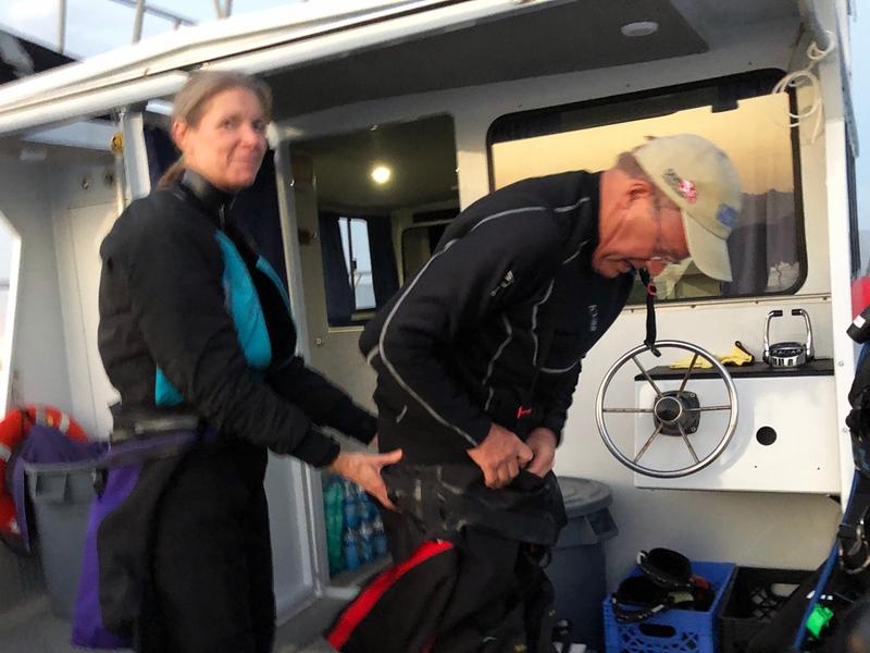 Nannette & Bill Van Antwerp donning drysuits.<br /> Giant Stride<br /> Black Water (night) dive, off Palos Verdes, California