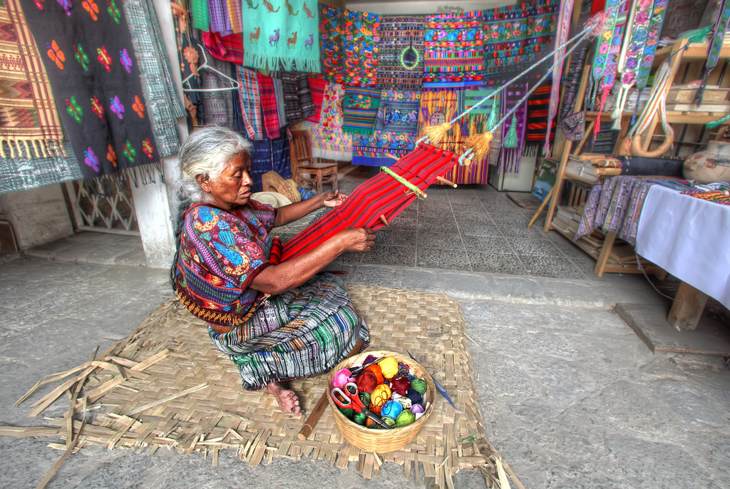 Mayan woman backstrap weaving surrounded by colorful weavings in antigua, guatemala