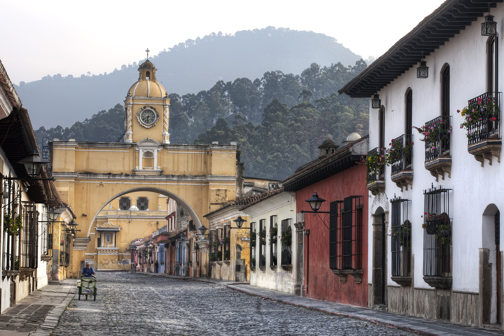 Yellow Santa Catalina arch Antigua Guatemala with the hills in the background and cobbled sreet in the foreground