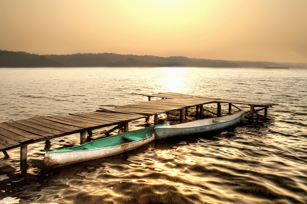 Two canoes tied to a dock on a golden morning in tikal, guatemala