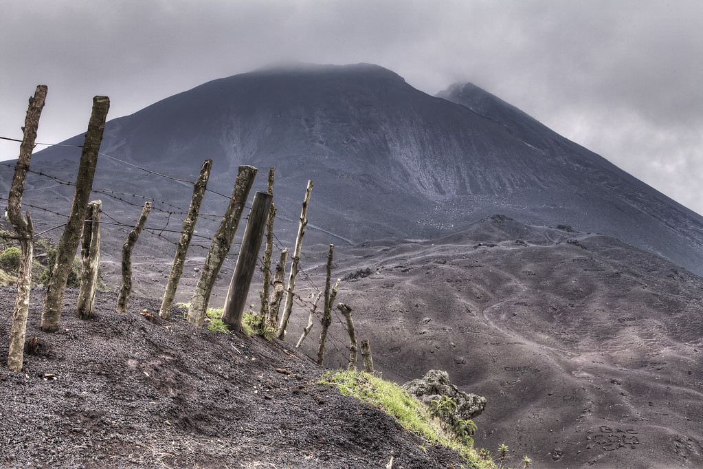 Pacaya volcano in guatemala on a cloudy day with a rough barb wired fence in the foregound