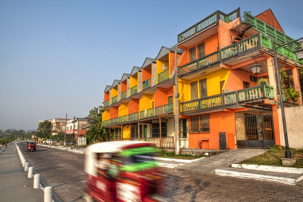 Tuk tuk in front of a colorful building in Flores Guatemala near Tikal