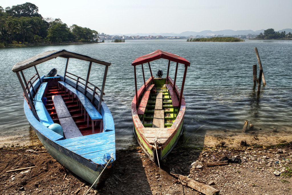 Two colorful launches on the shore of Lake Peten Itza near Flores in Guatemla