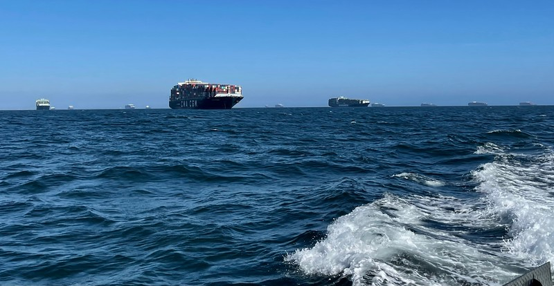 Dozens of shipping container ships, anchored in the Catalina Channel.<br /> San Pedro, Giant Stride<br /> March 18, 2021