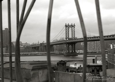 Manhattan Bridge through Bars of Brooklyn Bridge