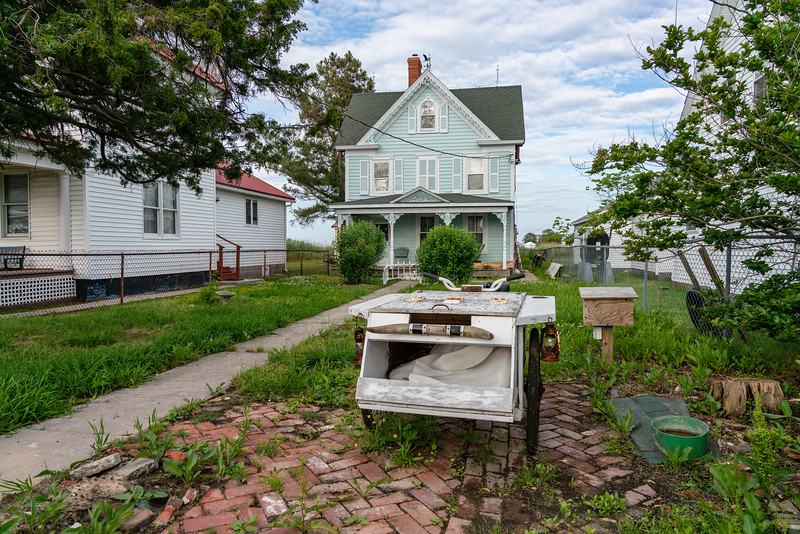 A charming victorian house with a bunch of crap in the front yard.