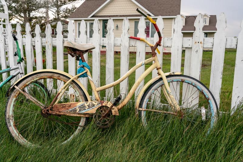 Rusty bike on fence.