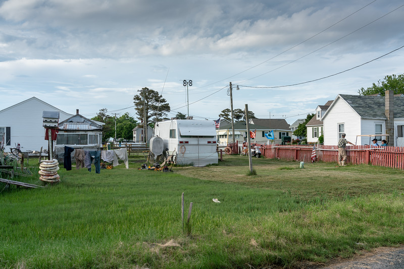 This tiny trailer is a waterman's home. He chats with neighbors while laundry hangs on the line.