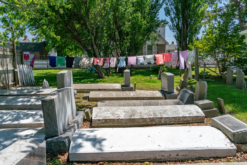 A backyard cemetery with laundry on the line.
