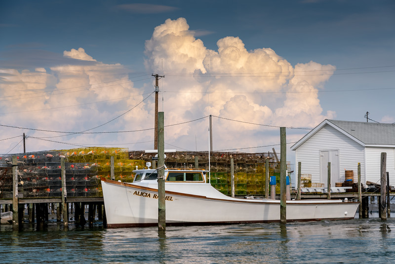 A classic Chesapeake Bay deadrise boat with storm clouds in the distance.