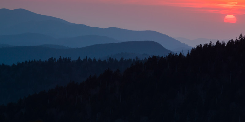 The sun peeks briefly from the clouds before sinking behind the mountains. Great Smoky Mountains National Park, NC<br /> <br /> NC-120414-0017