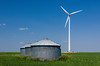 A windmill turbine and grain storage bins on a field in rural North Dakota, USA.