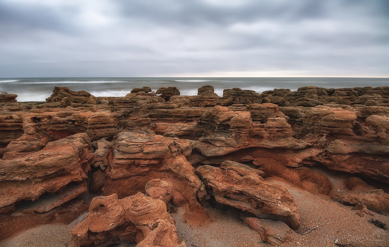 Overcast morning just before sunrise on a beach packed full of coquina rock