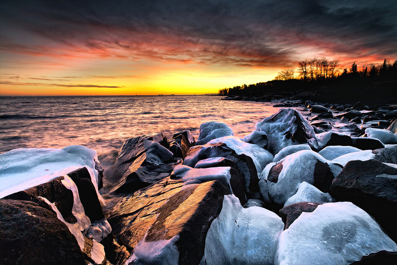 An early winter sunset bathes the frozen Lake Superior shoreline in warm light as viewed from Brighton Beach.