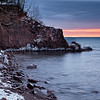 A path of white leads into a sunrise over Lake Superior.