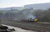 37419 Carl Haviland & 37611, 6Z50, Carnforth, Wed 26 March 2014 - 1007.  DRS's Crewe - Drigg flasks passes the site of F & M Junction.  The Furness & Midland joint line line at left used to connect the Furness Rly from Barrow with the Midland Rly's 'little North Western' line from West Yorkshire to Lancaster and Morecambe at Wennington.  The F & M line used to carry heavy freight traffic.  The Midland Rly's bottom end sidings are in the foreground.