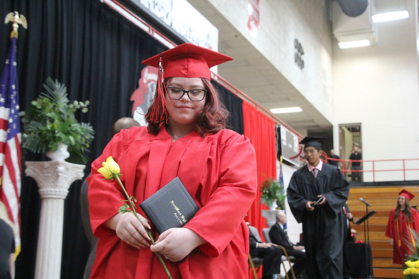 Bobby Stark carries her diploma and a flower as she walks off the stage during NorthWood High School's 2021 graduation ceremony in the school's gym in Nappanee on Friday.