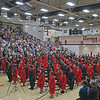 About 192 students in red and black caps and gowns stand, ready to receive their diplomas during NorthWood High School's 2021 graduation ceremony in Nappanee on Friday.