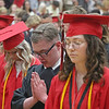 (center) Tristyn Null joins classmates in prayer during the start of NorthWood High School's 2021 graduation ceremony in Nappanee on Friday. To Null's right is classmate Grace Schmucker.