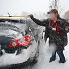 Chelmsford snow features. Michelle Parker of Chelmsford, who works at the Hannaford supermarket at Drum Hill, cleans off her car after her first day back at work after a vacation in Vermont. (SUN/Julia Malakie)