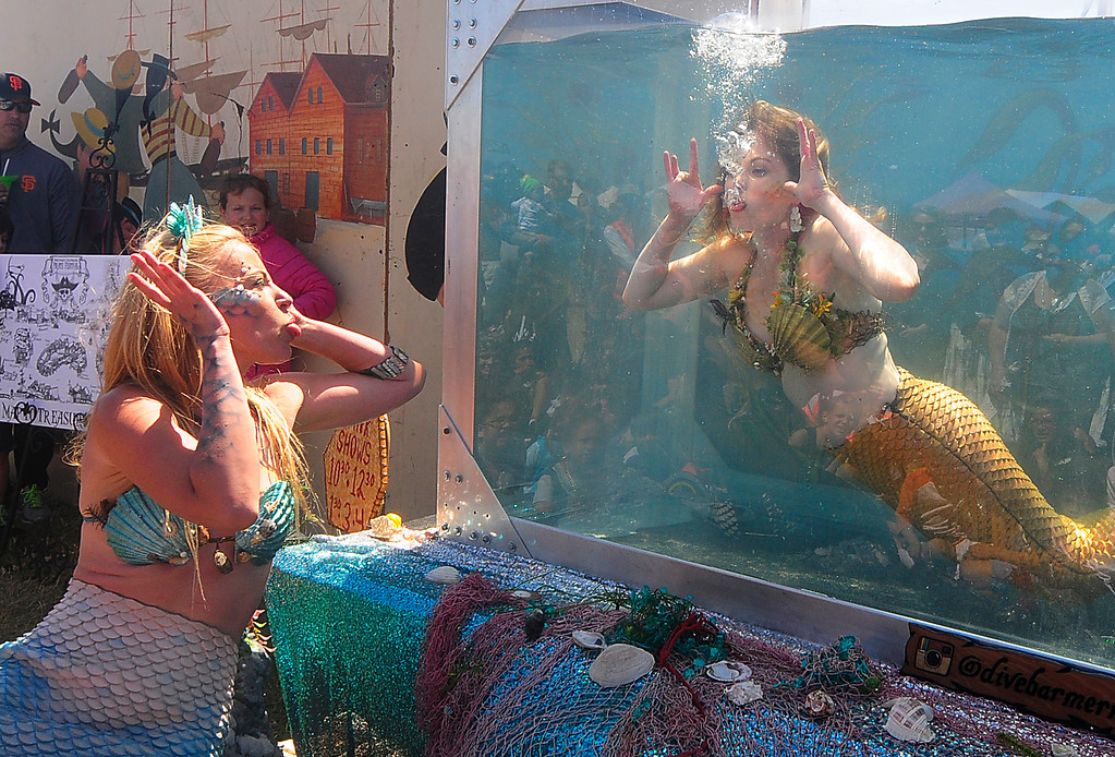. VALLEJO, CA - JUNE 16, Mermaid Rachel, left, and Mermaid Krista make faces at each other during the mermaid tank show at the Pirate Festival on Saturday. (CHRIS RILEY/TIMES-HERALD)