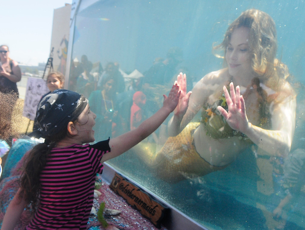 . VALLEJO, CA - JUNE 16, Mermaid Kirista high-fives a young pirate from inside the mermaid tank during the Northen California Pirate Festival along the waterfront in Vallejo on Saturday. (CHRIS RILEY/TIMES-HERALD)