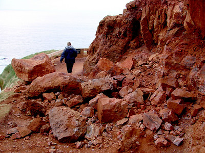 Debs negotiates her way around the rock fall on the path around the headland. The red rocks are made of volcanic Laterite.