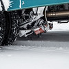This device is kind of a weed-whacker that clears snow from in front of the tires.