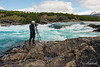 Photographer with tripod on rocks by Rio Baker and Rio and Neff confluencia, Patagonia, Chile