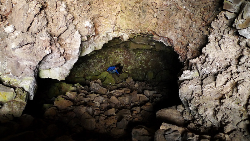 Checking out a sketchy cave. Can't go lower without a rope (old rotten wood planks above drop into deeper cave). Didn't have proper equipment along. Checked it out from above and moved on.
