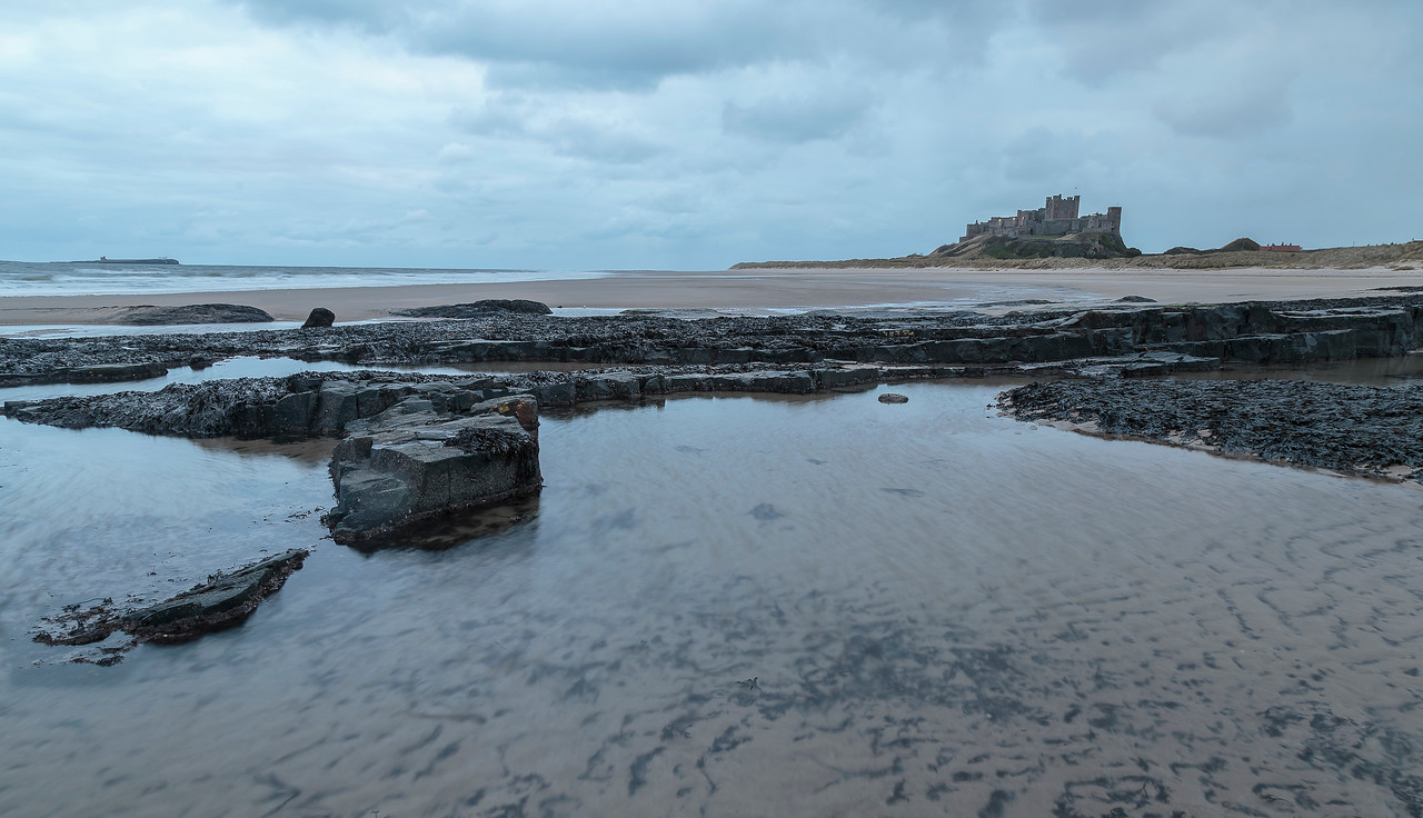 Bamburgh Castle from rocky ledge at dawn