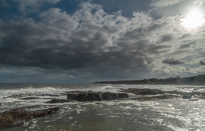 Cullernose Point - dramatic sky with waves breaking on basalt ledges