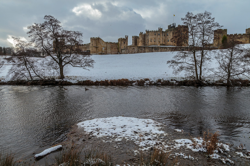 Alnwick Castle in snow across the River Aln