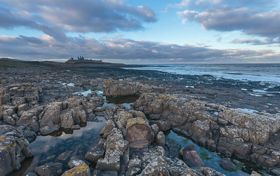 Dunstanburgh Castle with colourful sky reflections in rockpools