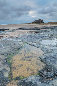 Bamburgh Castle from rockpool at dawn