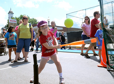 Shannen Sprenkel, 6, of Sunbury takes a swing at the ASA Softball booth Saturday Aug. 18, 2012 during the Sunbury River Festival.