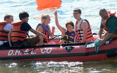"""Morgan Kerstetter, center, waves her shower cap to the crowd after being pulled with her teammates, Bethany Deppen and Matt Meyers, from the Susquehanna River when their boat """"Bathing Beauties"""" sunk during the Cardboard Boat Regatta Saturday Aug. 18, 2012 at the Sunbury River Festival."""