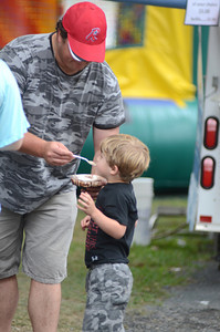 Jared Bednar, Shamokin, shares his ice-cream with his son, Jameson, 3, at the All Homes Days in Elysburg on Monday.