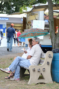 Nikki Lawrence, left, Danville, and Louis Mayan, Danville, sit on a bench under an umbrella at All Homes Days in Elysburg on a wet Monday afternoon.