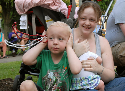 Gabe Palmer, 3, covers his ears while mom, Hope, covers his new sister, Sofie's, 7 weeks, ears as the fire trucks pass at the end of the Anthracite Heritage Festival of the Arts' parade Friday May 25, 2012 in Shamokin.